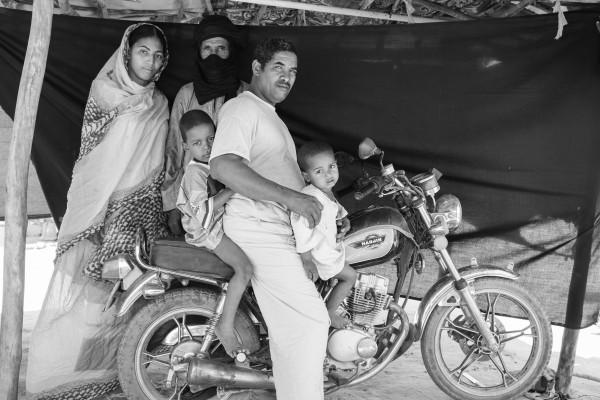 Abdou Ag Moussa, 34 años, está sentado junto a su familia sobre la moto que asegura que le salvó la vida. Brian Sokol / ACNUR