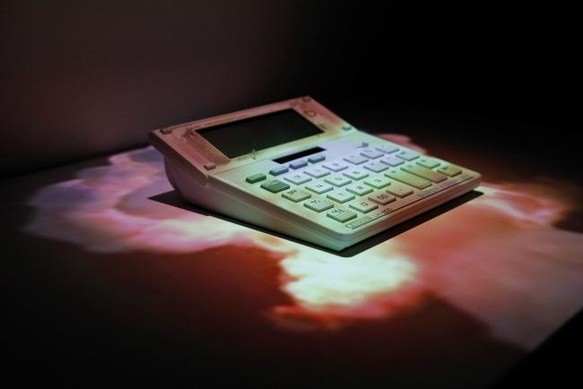 AC, 2014. Calculadora desechada, estante de madera, tarjeta de memoria MicroSD, videoproyección en bucle de 5:18 min. © Daniel Canogar. VEGAP Madrid, 2017 © Foto: Estudio Daniel Canogar – Cortesía de Sala Alcalá 31