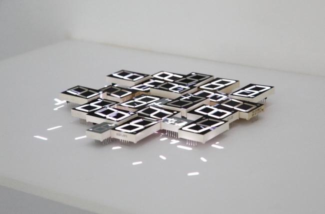 7 segmentos desechados, estante de madera, tarjeta de memoria MicroSD, videoproyección en bucle de 5:42 min. © Daniel Canogar. VEGAP Madrid, 2017© Foto: Estudio Daniel Canogar – Cortesía de Sala Alcalá 31