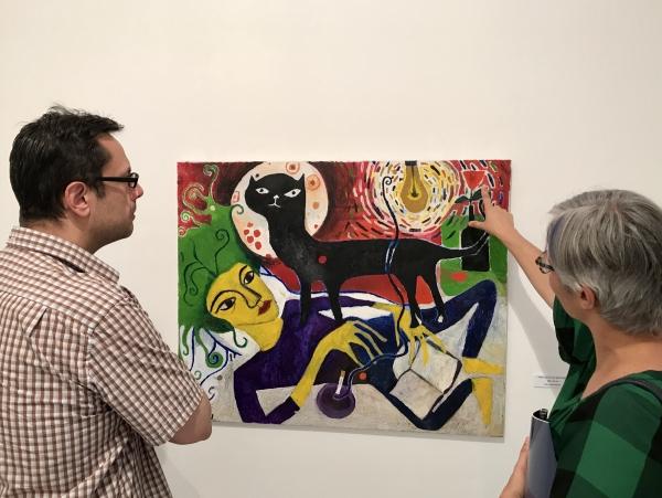 6. Una pareja comenta detalles del cuadro Mujer joven con gato negro