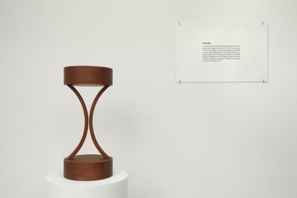 Iman Issa. Labouring (Study for 2012), 2012. Madera de caoba, panel de texto con cristal y podium de madera. Medidas variables