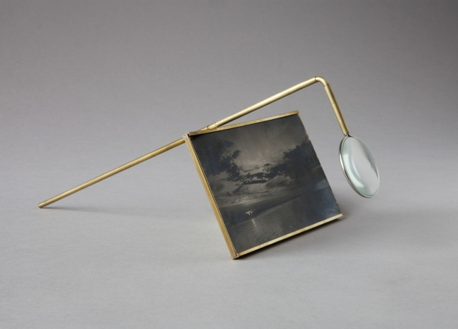 Juuso Noronkoski, Device no.5 (The Third Sun), 2017, sunlight on found photograph, 14 x 10 cm, brass, solder, magnifying glass. Edition- unique (from the series of 10 devices). – Cortesía de Alarcón Criado | Ir al evento: 'Overlapping Instants'. Exposición de Fotografía en Alarcón Criado Galería / Sevilla, España